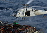 STK102351M © Stocktrek Images, Inc. Sailors attach pallets of supplies to an MH-60S Knighthawk.