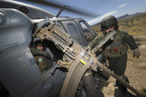STK103670M © Stocktrek Images, Inc. Soldiers prepare to reload a .50 caliber machine gun on an HH-60 Pave Hawk.