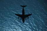 STK103768M © Stocktrek Images, Inc. Silhouette of a military aircraft in flight over the Atlantic Ocean.