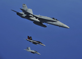 STK103774M © Stocktrek Images, Inc. A F/A-18C Hornet flies near two F/A-18F Super Hornet aircraft during a mission.