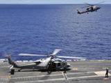 STK103802M © Stocktrek Images, Inc. SH-60 Sea Hawk helicopters land aboard the aircraft carrier USS Ronald Reagan.
