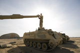 TMO100049M © Stocktrek Images, Inc. A US Army mechanic uses a M113 as a platform to boresight a M1 Abrams tank.