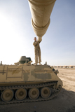 TMO100051M © Stocktrek Images, Inc. A US Army mechanic uses a M113 as a platform to boresight a M1 Abrams tank.