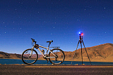 JFD200045S © Stocktrek Images, Inc. A camera, tripod and bicycle on a full moon night at Yamdrok Lake, Tibet, China.