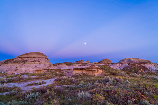 ADY200188S © Stocktrek Images, Inc. Gibbous moon and crepuscular rays over Dinosaur Provincial Park, Canada.