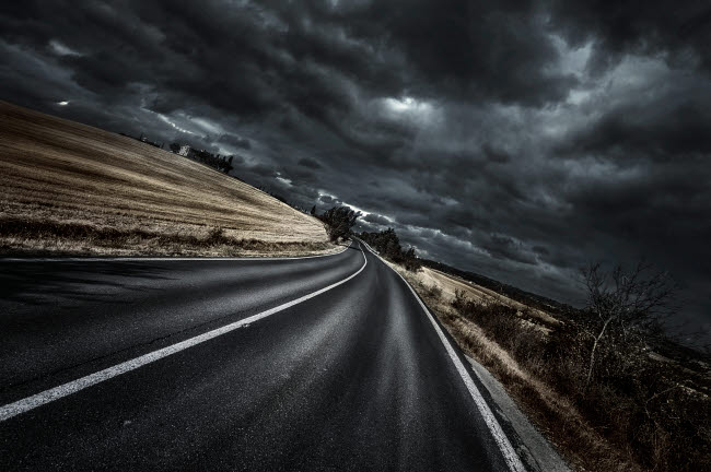 EVK200223S © Stocktrek Images, Inc. An asphalt road with stormy sky above, Tuscany, Italy.