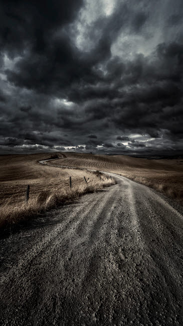 EVK200229S © Stocktrek Images, Inc. A country road in field with stormy sky above, Tuscany, Italy.