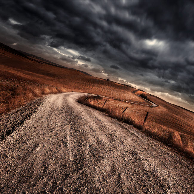 EVK200230S © Stocktrek Images, Inc. A country road in field with stormy sky above, Tuscany, Italy.