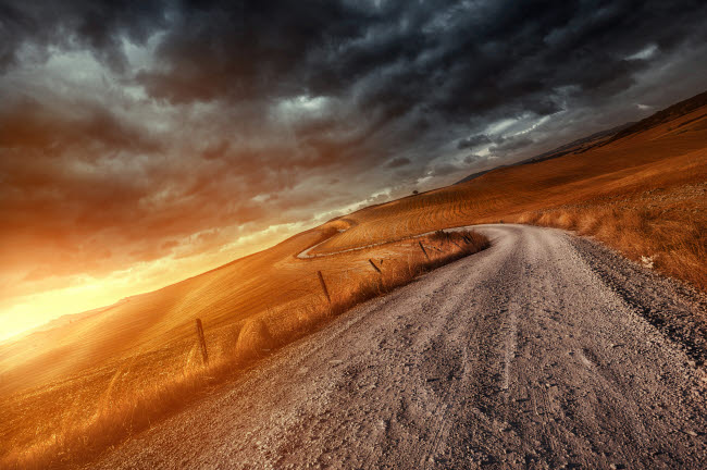 EVK200231S © Stocktrek Images, Inc. A country road in field at sunset against stormy clouds, Tuscany, Italy.