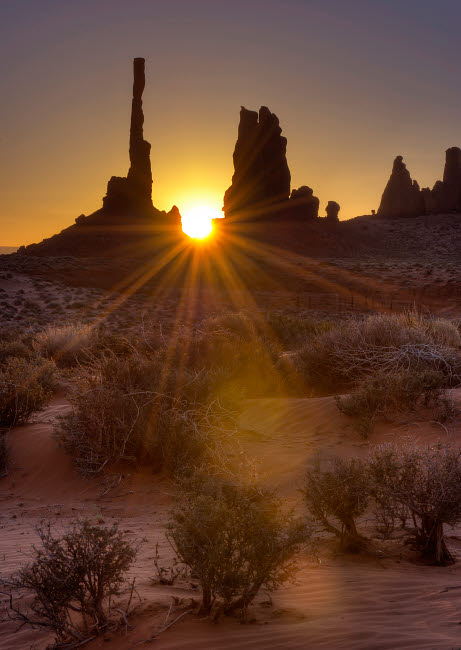 JDA100031S © Stocktrek Images, Inc. Sunburst through the Totem Pole formation in Monument Valley, Utah.