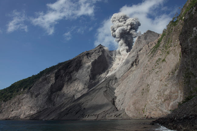 RRS300494S © Stocktrek Images, Inc. Ash cloud rises from crater of Batu Tara volcano, Indonesia.
