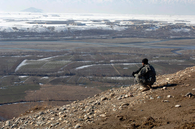 STK102230M © Stocktrek Images, Inc. U.S. Army Soldier looks out over the village of Dingak, Afghanistan.