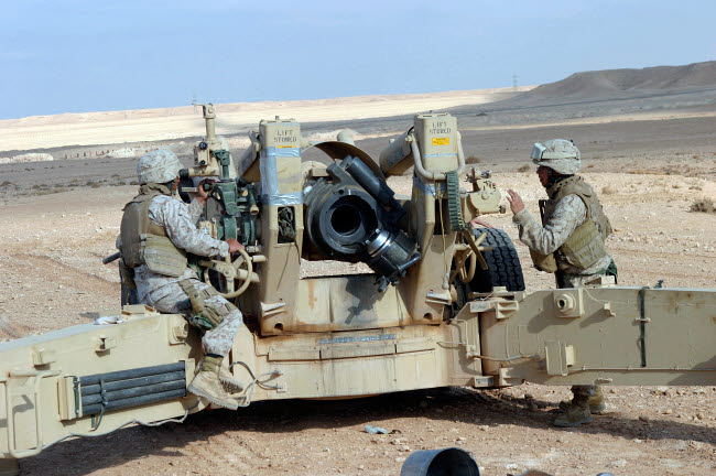 STK102234M © Stocktrek Images, Inc. U.S. Marines prepare to fire a howitzer near Baghdad, Iraq.