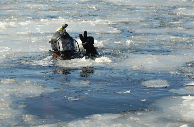 STK102252M © Stocktrek Images, Inc. U.S. Navy Diver signals he is okay during a training mission in the icy Thames River.