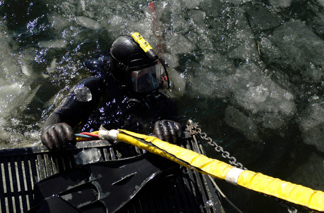 STK102253M © Stocktrek Images, Inc. U.S. Navy Diver gets ready to start his dive off the back of a dive training boat.