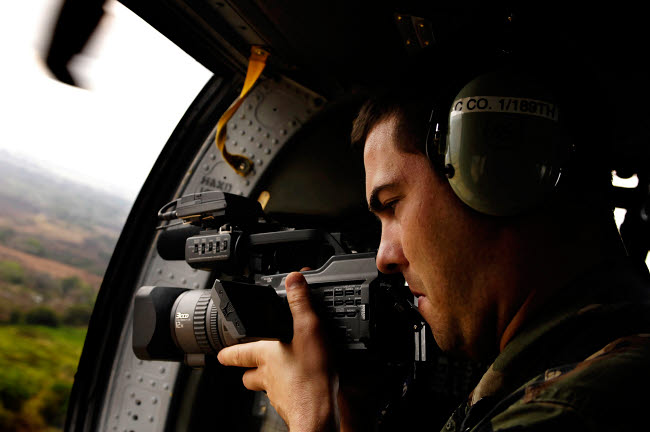 STK102348M © Stocktrek Images, Inc. U.S. Air Force Airman takes video aboard a U.S. Army UH-60A Black Hawk.