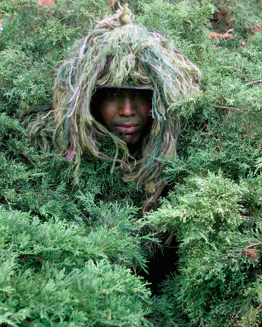 STK102376M © Stocktrek Images, Inc. U.S. Army Soldier demonstrates the use of the camouflage Ghillie Suit.