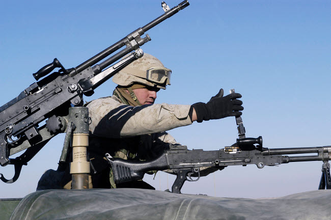 STK102399M © Stocktrek Images, Inc. A U.S. Marine Corps troop loads his FNMI 7.62 mm M240 Machine Gun.