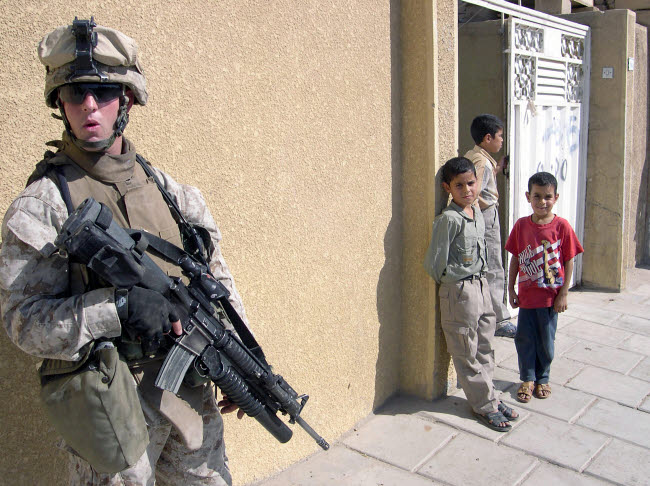 STK102401M © Stocktrek Images, Inc. A group of Iraqi children observe a U.S. Marine armed with a 5.56mm M16A2 rifle.