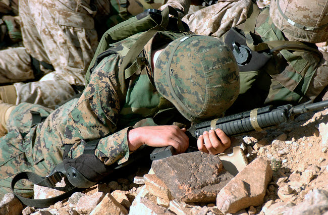STK102402M © Stocktrek Images, Inc. U.S. Marine Corps Private takes cover, protecting his 5.56 mm M16A2 rifle.