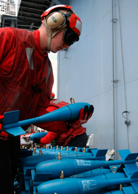 STK102412M © Stocktrek Images, Inc. U.S. Navy Aviation Ordnanceman prepares inert training bombs.