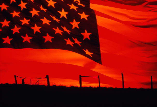 STK103447M © Stocktrek Images, Inc. Digital composite of the American Flag over the countryside.
