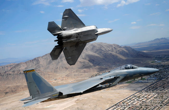 STK103803M © Stocktrek Images, Inc. An F-22 Raptor aircraft turns away while an F-15 Eagle flies the approach over Nevada.
