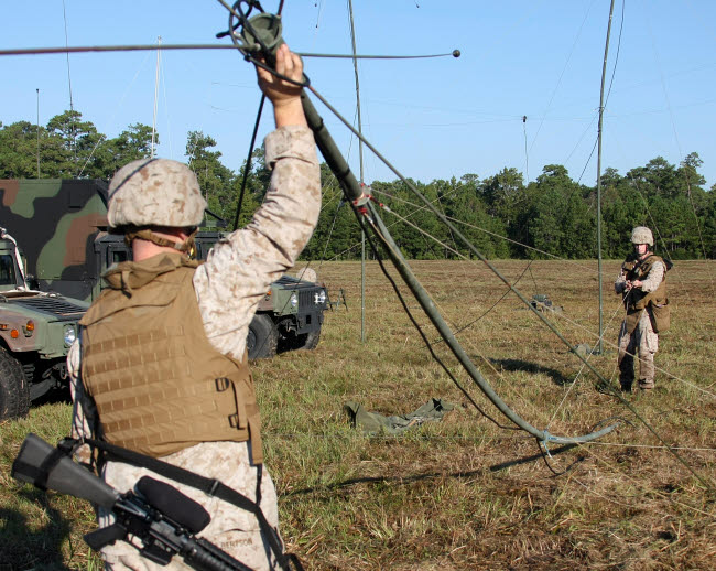 STK104032M © Stocktrek Images, Inc. Marines raise an OE-254 field radio antenna during a communications exercise.