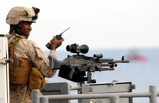 STK104038M © Stocktrek Images, Inc. U.S. Marine talks on a radio while manning an M-240B machine gun.