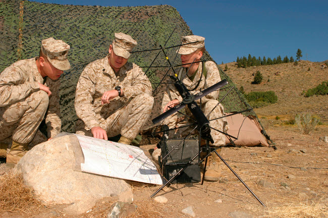 STK104043M © Stocktrek Images, Inc. Soldiers analyze the finer points of a terrain map at a radio communications center.
