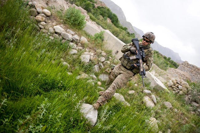 STK106281M © Stocktrek Images, Inc. U.S. Army Specialist walks through a field in Afghanistan.