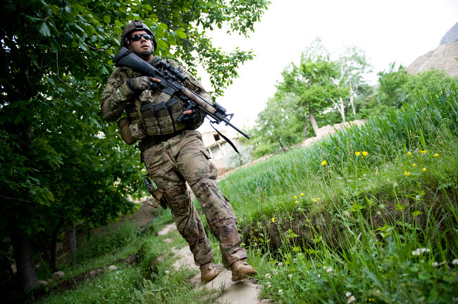 STK106282M © Stocktrek Images, Inc. U.S. Army Specialist walks through a field in Afghanistan.