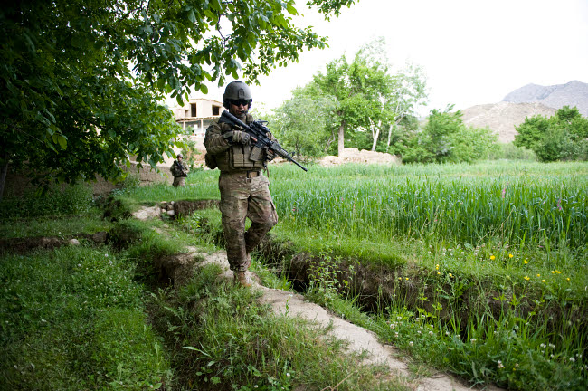 STK106283M © Stocktrek Images, Inc. U.S. Army Specialist walks through a field in Afghanistan.