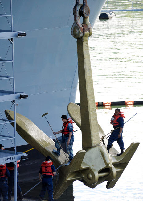 STK106380M © Stocktrek Images, Inc. Sailors paint the starboard anchor of the aircraft carrier USS Nimitz.