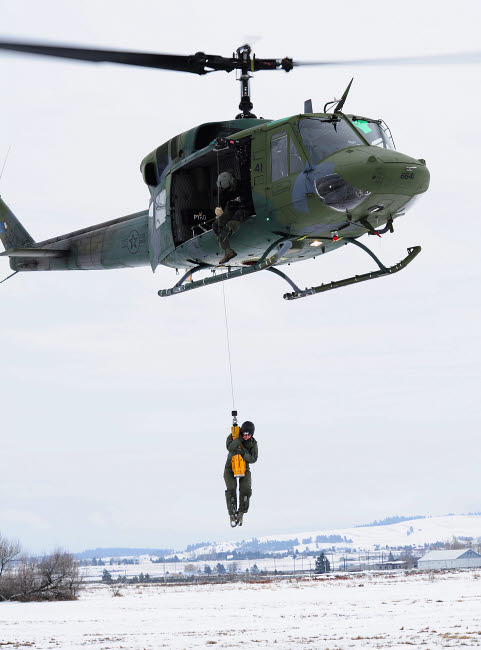 STK106743M © Stocktrek Images, Inc. A student is hoisted into a UH-1N Iroquois during a training exercise.