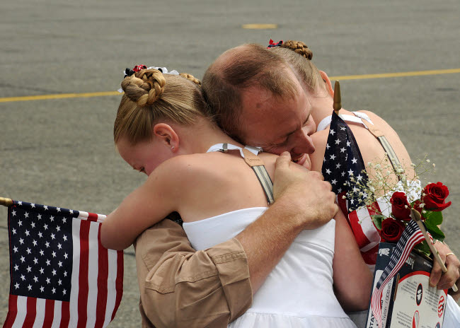 STK107963M © Stocktrek Images, Inc. A flight engineer is greeted by his daughters during homecoming.
