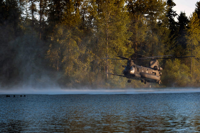STK108369M © Stocktrek Images, Inc. Airmen wait in a lake for an MH-47 Chinook helicopter to extract them.