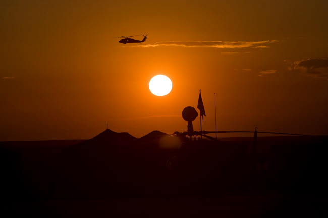 TMO100001M © Stocktrek Images, Inc. UH-60 Blackhawk flies over Camp Speicher airfield at sunset.