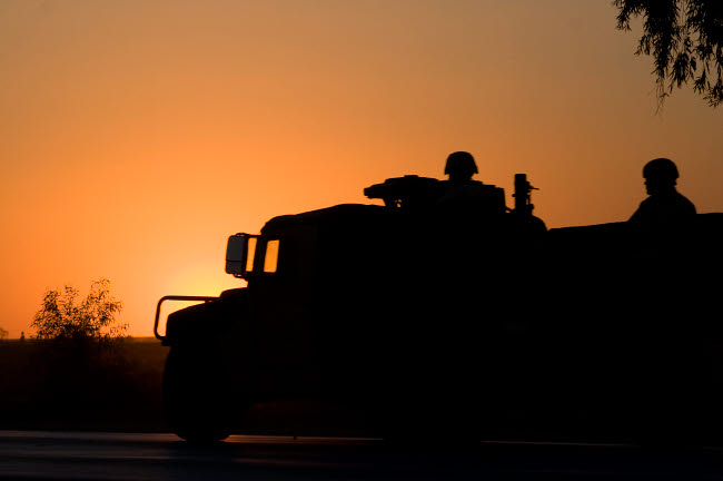 TMO100018M © Stocktrek Images, Inc. A U.S. Army Humvee with soldiers in the back at sunset.