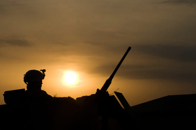 TMO100079M © Stocktrek Images, Inc. A US Soldier mans his .50 caliber while waiting to move out on a mission at sunset.