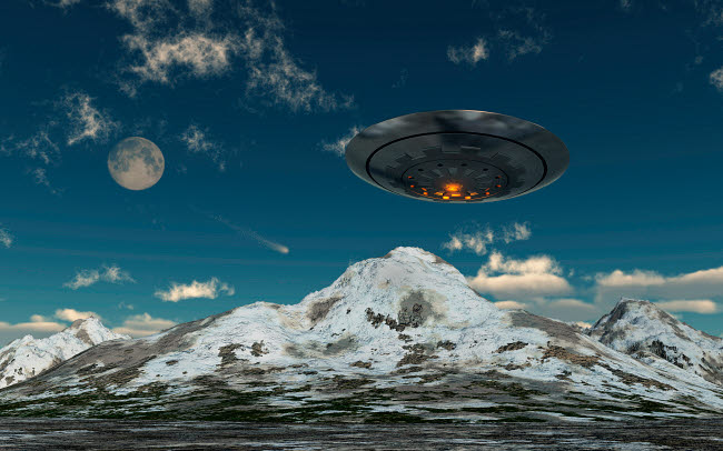MAS200057S © Stocktrek Images, Inc. A UFO flying over a mountain range.