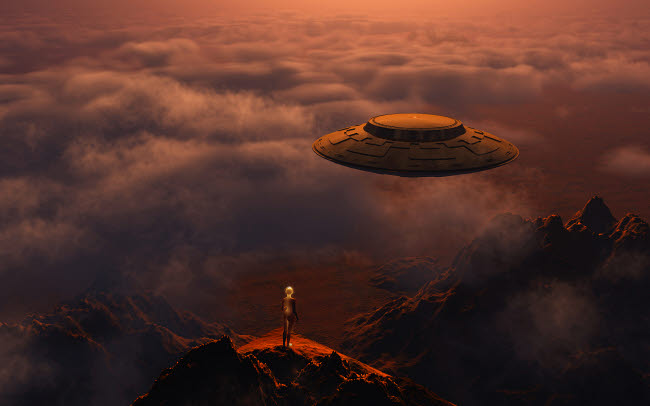 MAS200196S © Stocktrek Images, Inc. A robotic cyborg standing on a mountain ledge as a flying saucer flies above.
