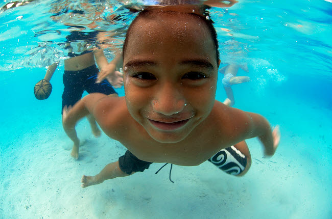 AAW400002U © Stocktrek Images, Inc. Local boy in shallow lagoon in Bora Bora, French Polynesia.