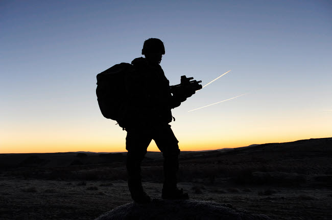 ACH100553M © Stocktrek Images, Inc. A British soldier on patrol as the Sun rises.