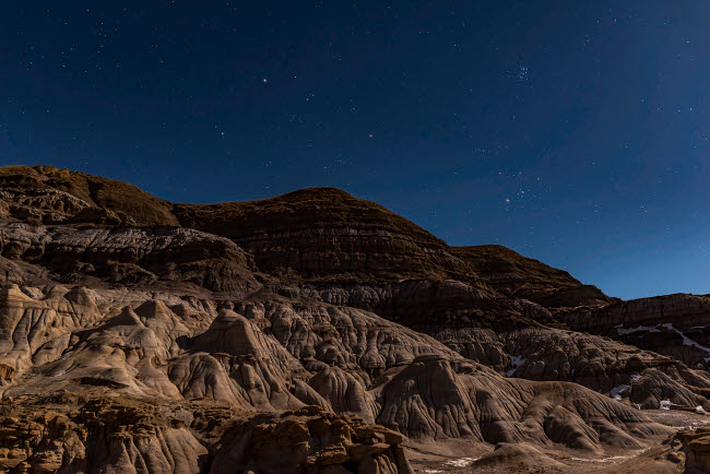 ADY200362S © Stocktrek Images, Inc. Auriga and Taurus rising in the moonlight at the Hoodoos near Drumheller, Alberta, Canada.