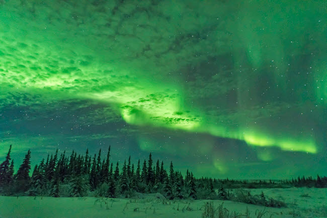 ADY200367S © Stocktrek Images, Inc. A brightening aurora behind thin clouds lighting the clouds and ground green.