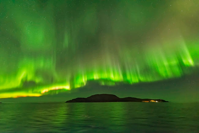ADY200447S © Stocktrek Images, Inc. Northern lights over an island along the Norwegian coast.