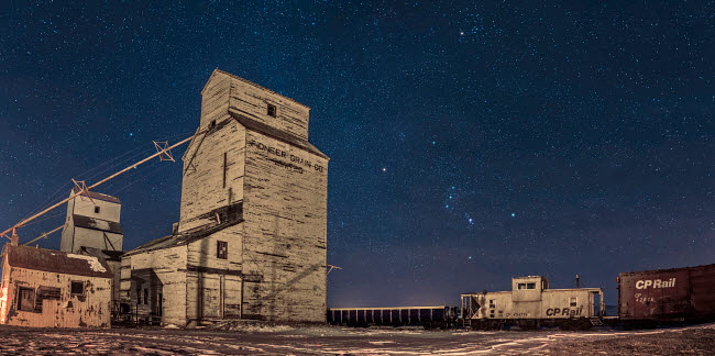ADY200456S © Stocktrek Images, Inc. Orion and the winter stars rising behind grain elevators in Mossleigh, Canada.