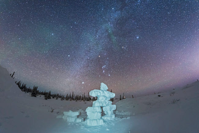 ADY200457S © Stocktrek Images, Inc. Milky Way and winter stars over a mock-up inukshuk figure made of snow, Canada.