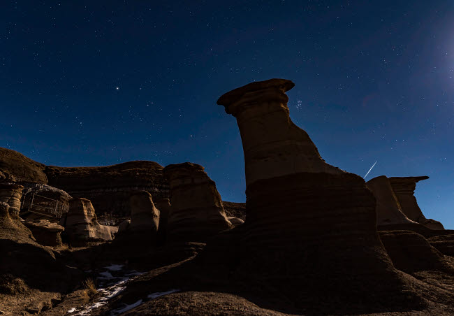 ADY200474S © Stocktrek Images, Inc. The Pleiades appearing from behind the Hoodoos in silhouette.